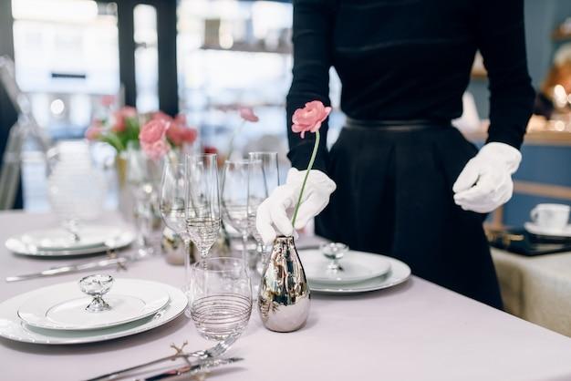 空の食器、テーブルの設定に対するウェイトレス。サービングサービス、お祝いディナーデコレーション、ホリデーディナーウェア