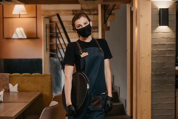 Waitress in black disposable medical gloves wears a medical face mask
