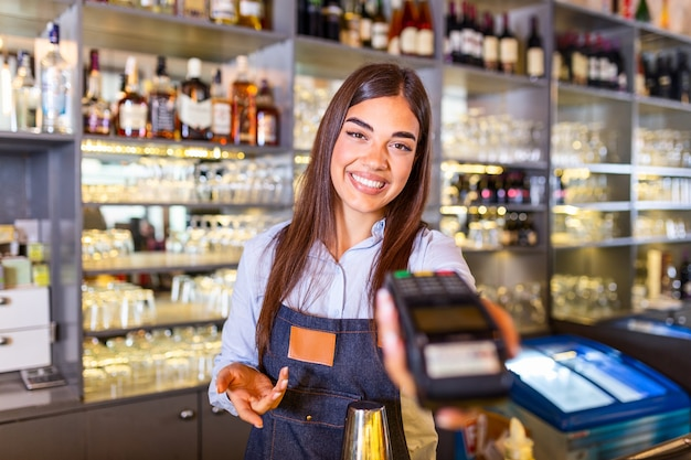 Waitress at cash counter holding an electronic card payment machine.