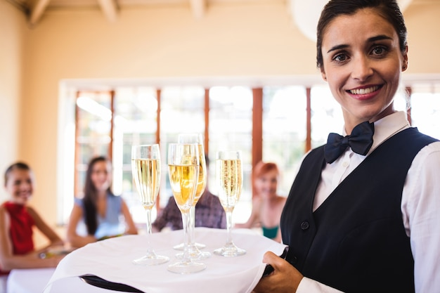 Waitress champagne glasses on tray in restaurant