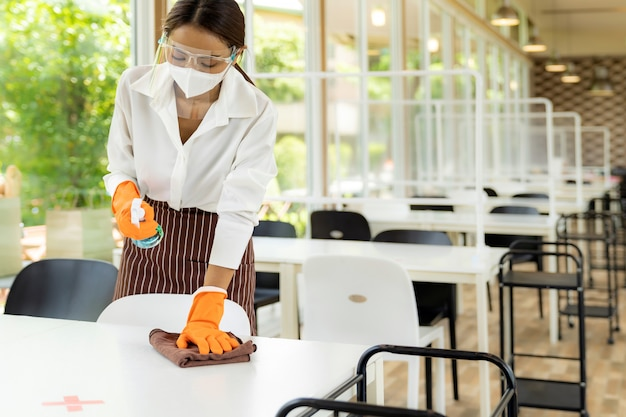Waitress cleaning table, new normal restaurant concept