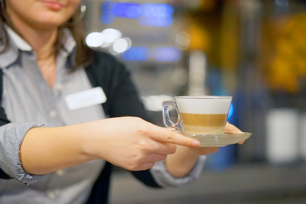 The waitress gives a cup of coffee-cappuccino to a client in a restaurant. the concept of service and maintenance.