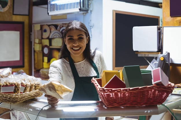 Waitress giving parcel at counter in cafe