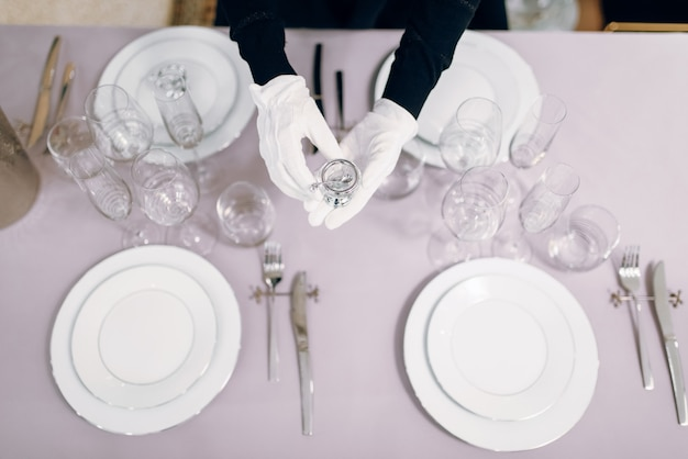 Waitress in gloves puts the dishes, table setting, top view. serving service, festive dinner decoration, holiday dinnerware