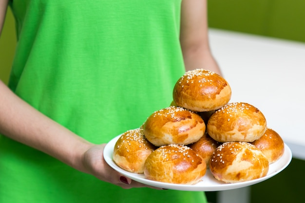 Waitress in a green uniform holding a plate with fresh tasty buns with sesame in cafe