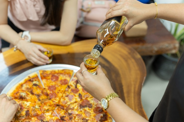 Waitress hand serving whiskey in small glasses shot for customer.