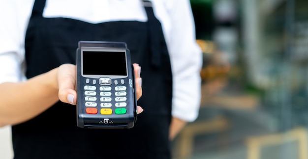 Waitress hand show electronic banking money machine for receive purchase from customer at restaurant