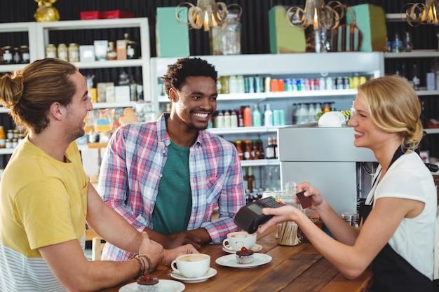 Waitress handing credit card machine to customer
