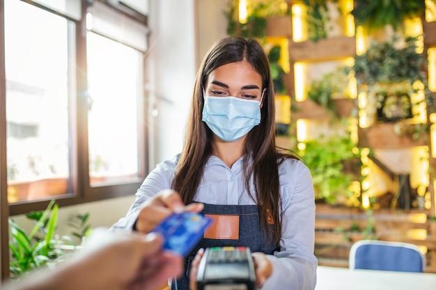 Официантка держит устройство для чтения кредитных карт и носит защитную маску