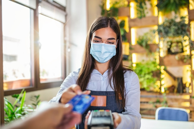 Waitress holding credit card reader machine and wearing protective face mask