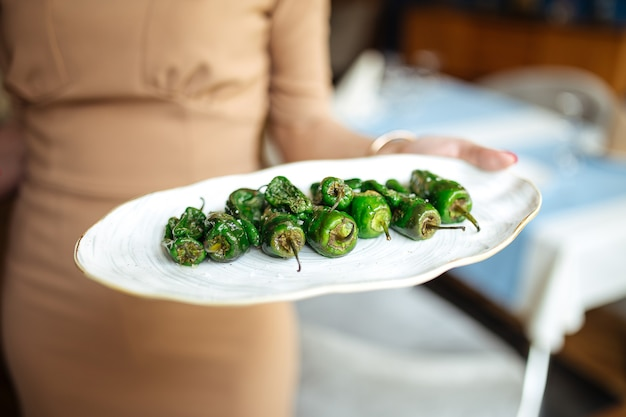 Waitress holding grilled spanish green padron peppers