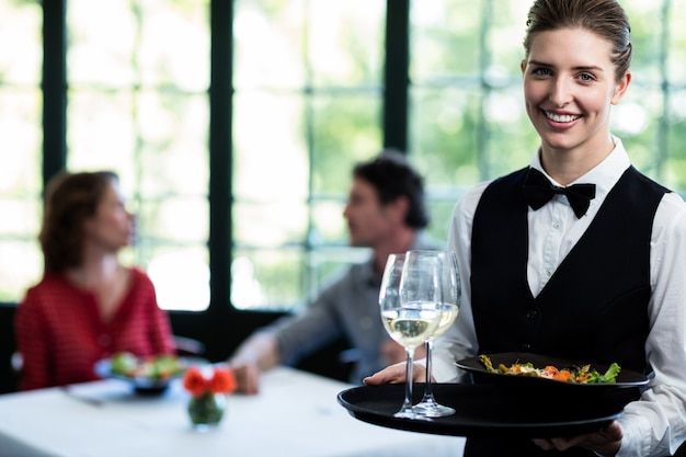 Waitress holding meal and wine glasses in restaurant