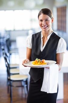 Официантка держит тарелку в ресторане