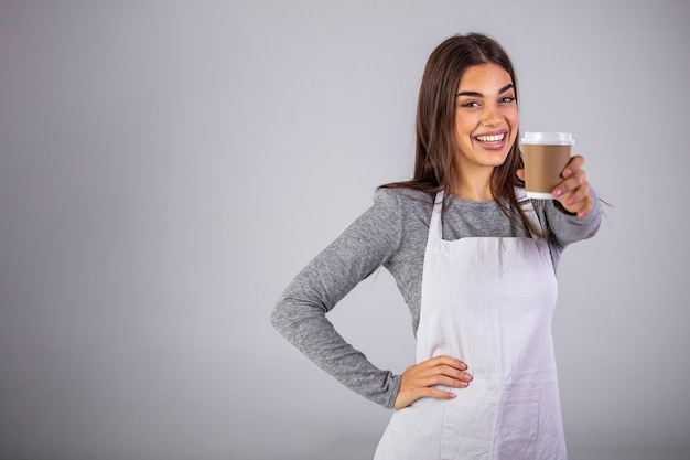A waitress holding and serving a paper cup of hot coffee on gray