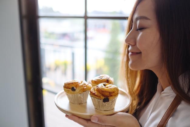A waitress holding and smelling raisin danish dessert
