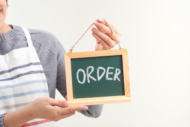 Официантка держит знак заказа на доске на белом фоне