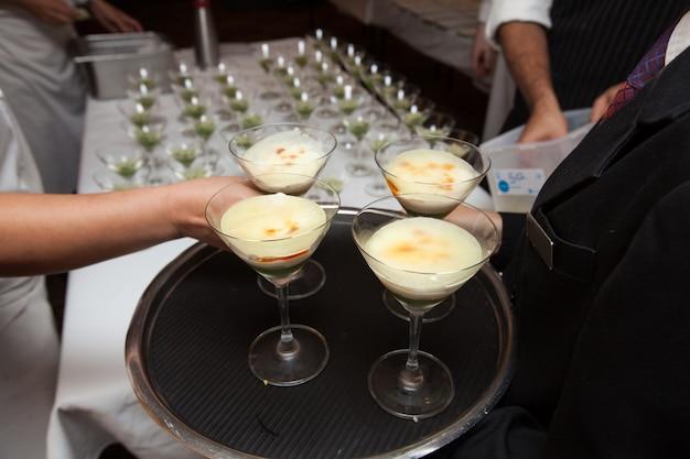 Официантка, держащая лоток десерта на ужин в ресторане ресторана ресторана