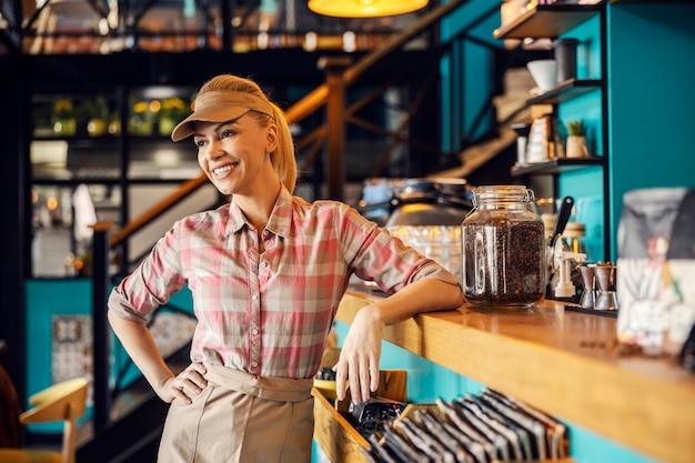 Официантка в кафе. портрет молодой красивой официантки в современной униформе, стоящей с улыбкой в кафе, прислонившись к стойке с банкой кофейных зерен. обслуживание в кафетерии