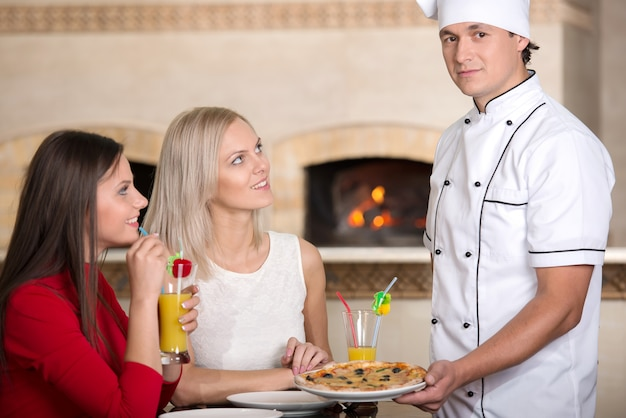 Waitress is giving pizza to a smiling woman at the pizzeria.