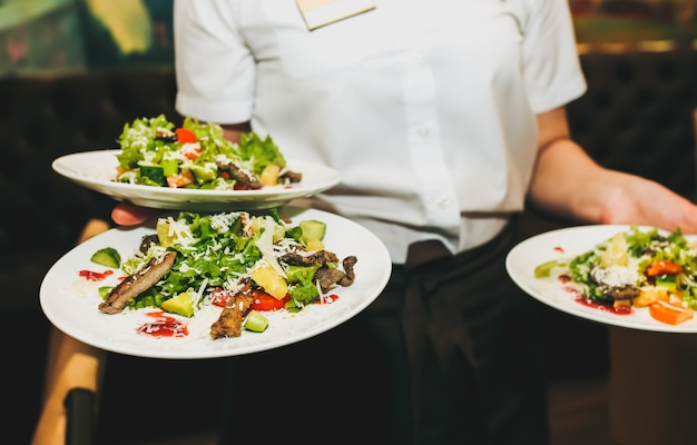 웨이트리스가 손에 신선한 샐러드 접시를 들고 있습니다. 여자는 레스토랑에서 테이블을 설정합니다. 생일이나 결혼 축하를 위한 카페 서비스. 제공되는 테이블에 다른 요리입니다.