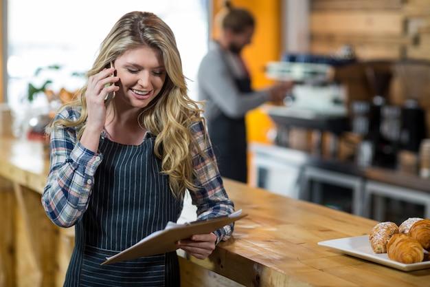 커피에서 휴대 전화로 이야기하는 동안 클립 보드를보고 웨이트리스