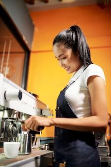 Waitress making coffee in coffee shop