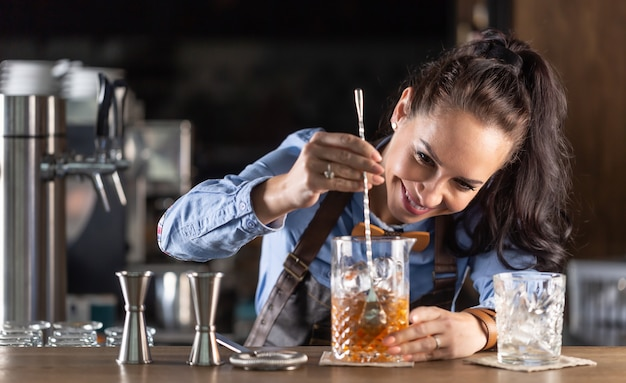 Waitress mixes old fashioned whiskey cocktail in a decorative glass in a pub.