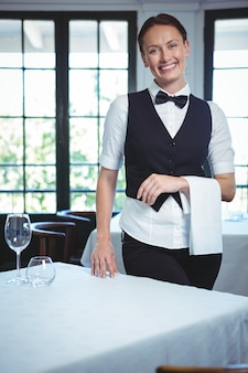 Waitress posing next to the table