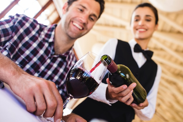 Waitress pouring red wine in wine glass at table