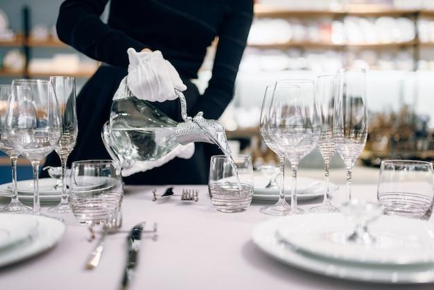 ウェイトレスがグラスに飲み物を注ぐ、テーブルセッティング
