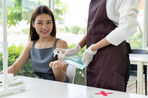 Waitress push hand sanitizer for customer.