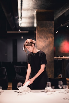 Waitress putting plate and napkin on table