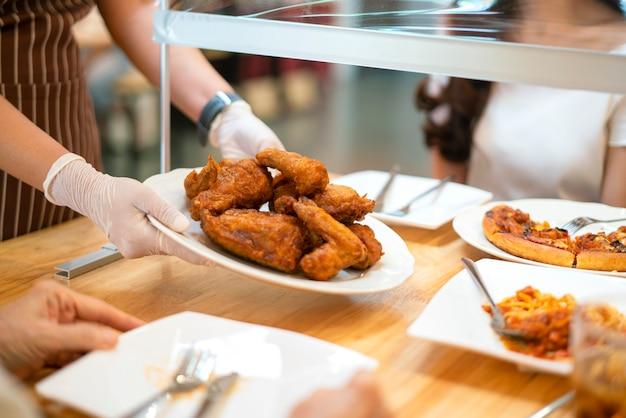 웨이트리스는 플라스틱 쉴드 파티션, 새로운 일반 및 사회적 거리를 두어 테이블에서 고객에게 음식을 제공합니다.