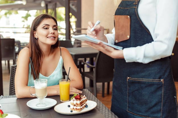 Waitress server helping client in cafe