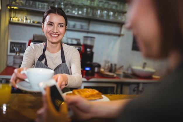 Стюардесса выступающей чашку кофе к клиенту
