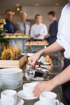Официантка сервировки кофе в ресторане со шведским столом