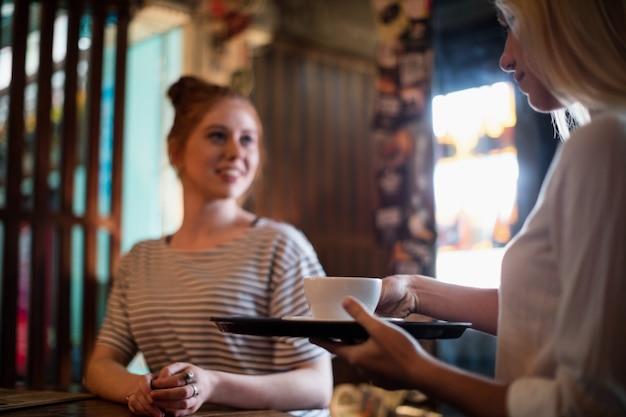 Официантка подает кофе женщине