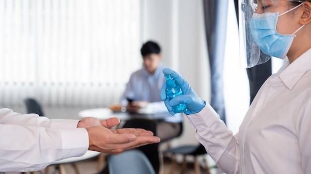 Waitress staff using disinfectant spray alcohol or gel to prevent the spread of pandemic covid-19