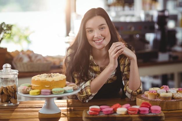 Официантка стоит у стойки с десертами