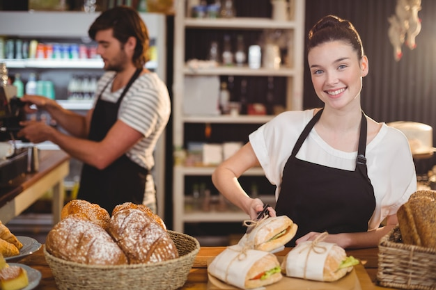 Waitress standing at counter with sandwiches and bread roll