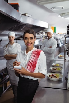 業務用厨房のキッチンスタッフと立っているウェイトレス