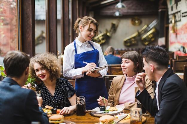 Официантка принимает заказы от людей в ресторане