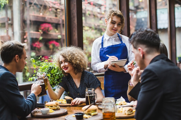 Waitress taking orders from people in restaurant