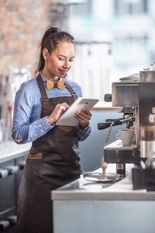 ウェイトレスは、コーヒーメーカーでエスプレッソが完成するのを待つ間、タブレットを使用します。