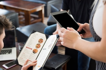 Waitress using digital tablet while taking order at restaurant