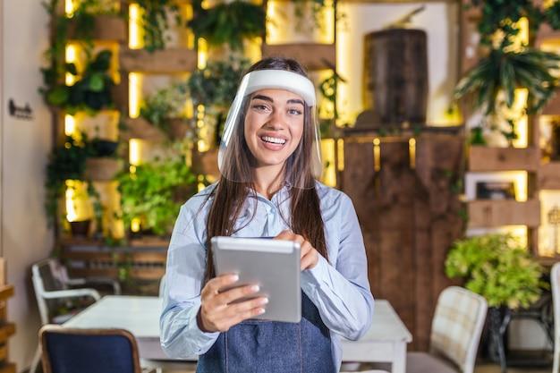 Waitress using digital tablet while wearing visor at the restaurant