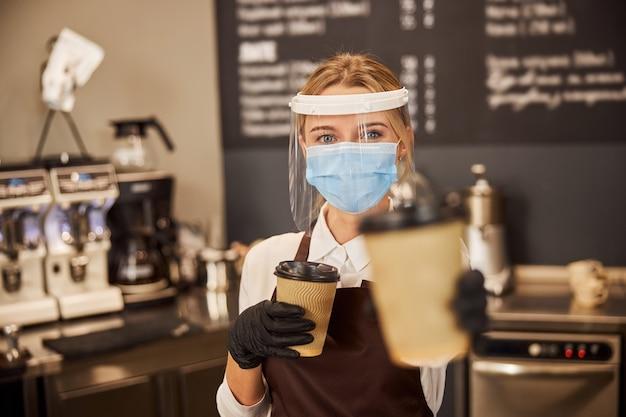 職場で医療用マスクとゴム手袋を着用しているウェイトレス。彼女の手に行くための2つの紙コップのコーヒー