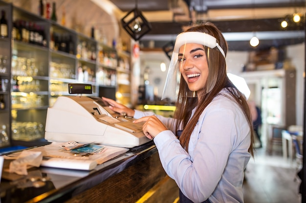 Waitress wearing an apron standing by a point of sale terminal and laughing while working in a restaurant. beautiful woman wearing face shield during coronavirus pandemic standing by cash register