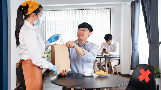 Официантка в маске для защиты от вспышки эпидемического вируса коронавирусной болезни