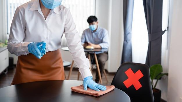 Официантка в перчатках, маске и столе для чистки защитной маски